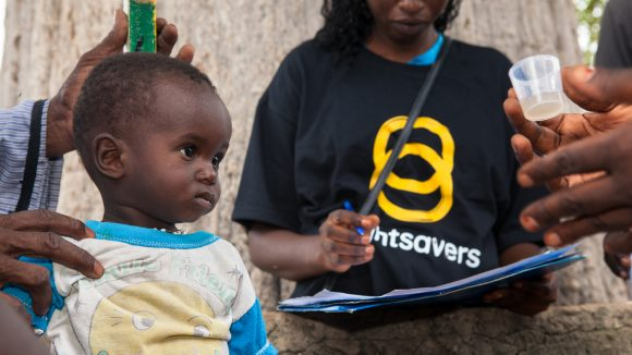 A young child is being measured for a dose of medication