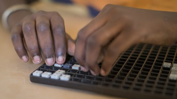 Close-up photo of hands reading braille.