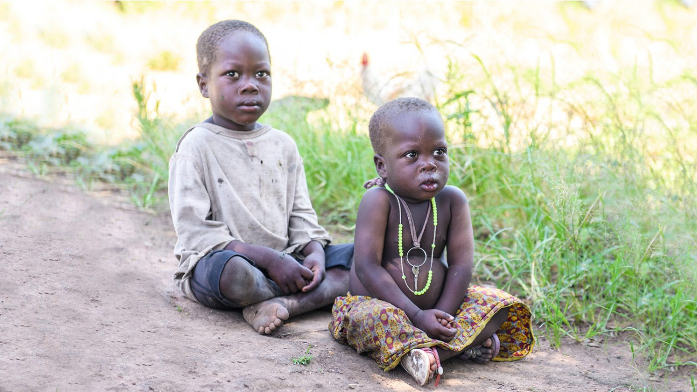 Young Adoc and Obali sit on the floor in their village.
