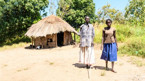 Ayenyo and Lawino stand together outside their hut in Uganda.
