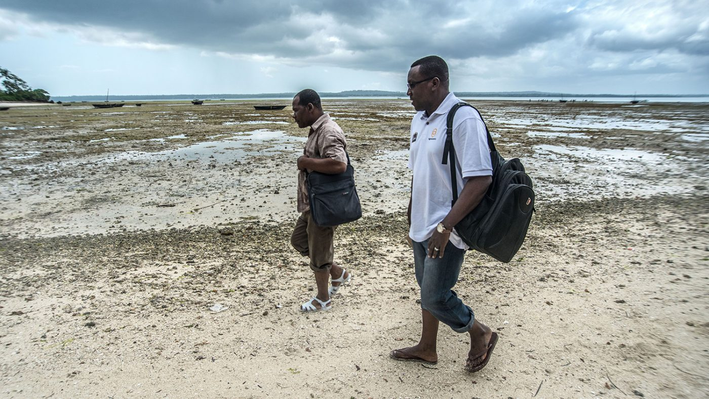 Dr Rajab and another health worker walk along the shore towards Jongowe school.