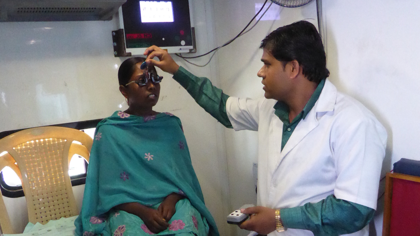 A woman has her eyes examined by a male ophthalmologist.