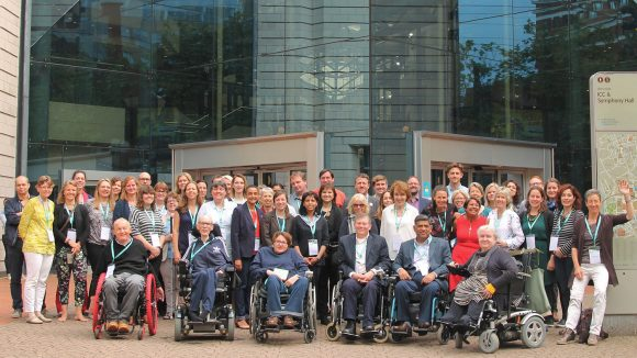 A large group of people with and without disabilities, outside a conference centre.