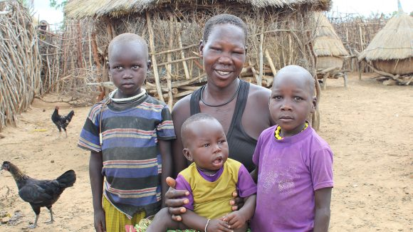 Margaret Adome sitting outside her home with three of her six children.