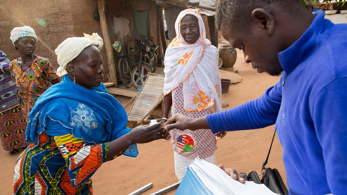 Mariam gets the correct amount of treatment for a lady in her village, who has just been measured.