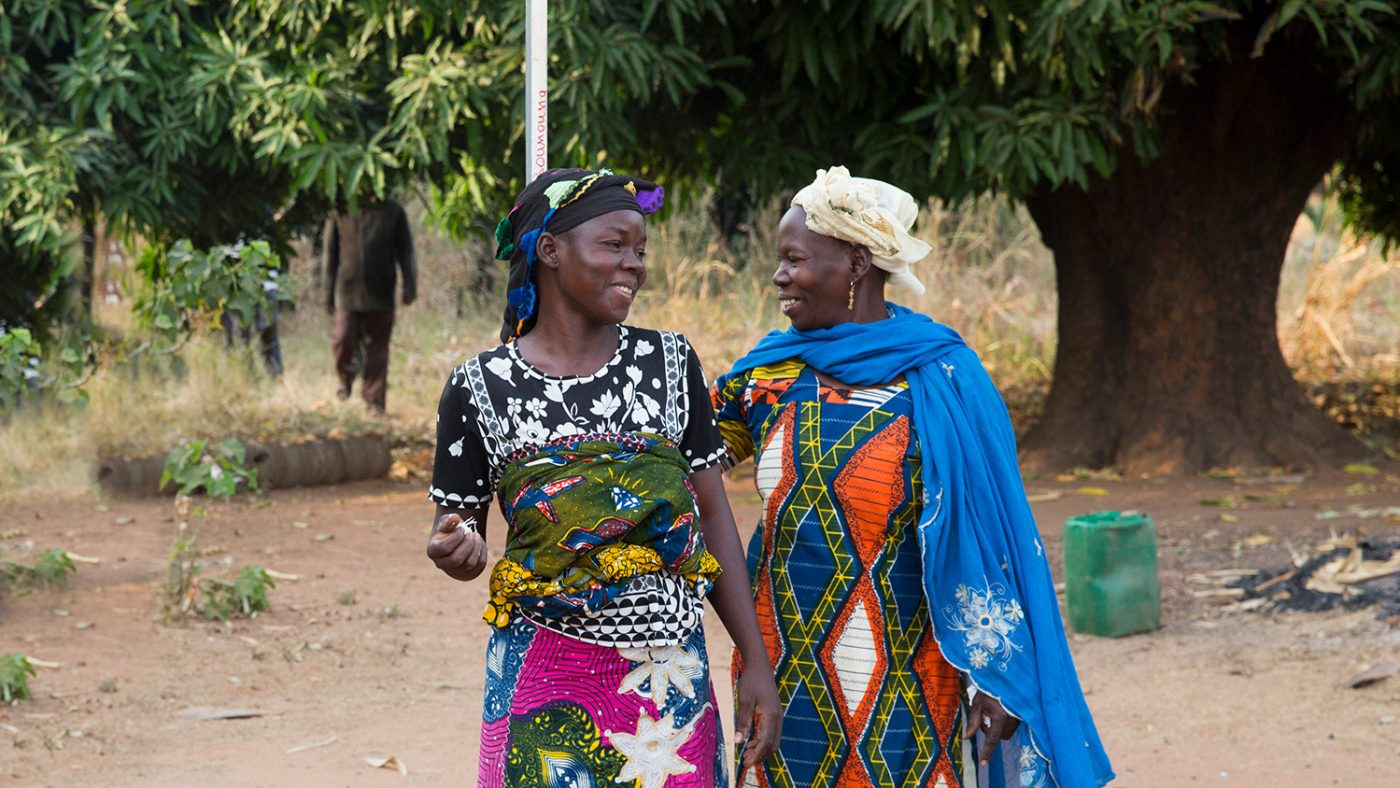 Mariam measures a lady in her village against a dose pole.