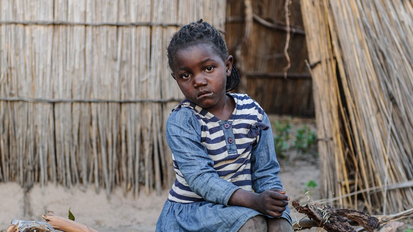 Young Matamola sits on a log alone on the dusty ground of her village in Zambia.
