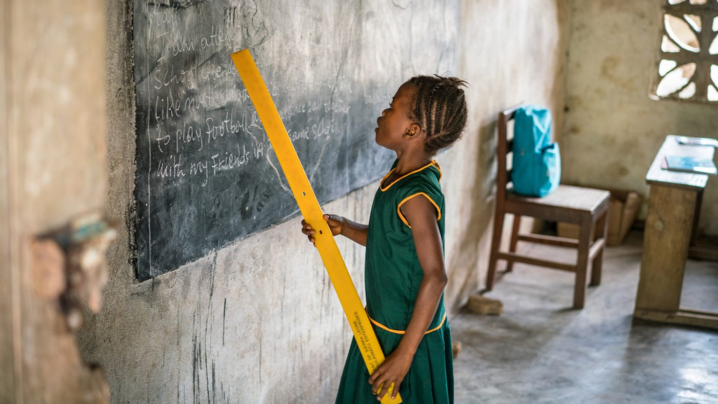 Aminata stands at the blackboard, holding a ruler to point out words.
