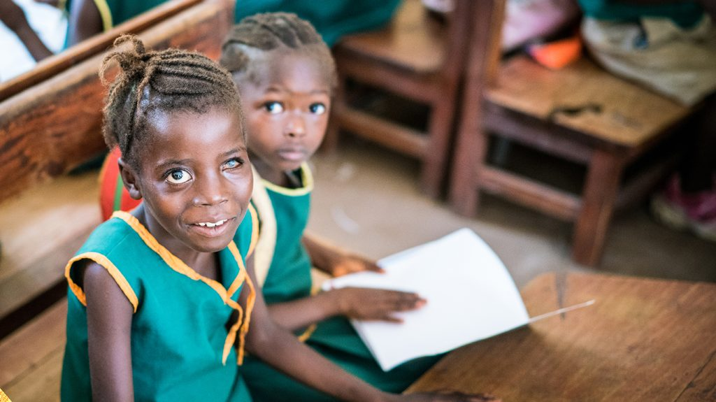 Aminata, who has visual impairments, sits at her school desk alongside a fellow student.