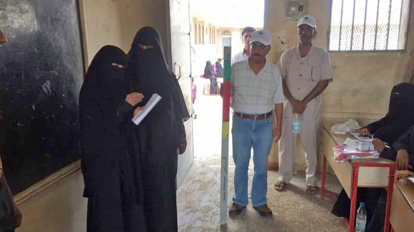 Two female health workers wearing face veils distribute trachoma treatments in Yemen.