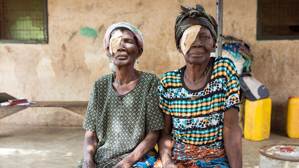 Sisters Barikisu and Ayishetu sit outside their home with bandages covering their eyes, following their trachoma operation.