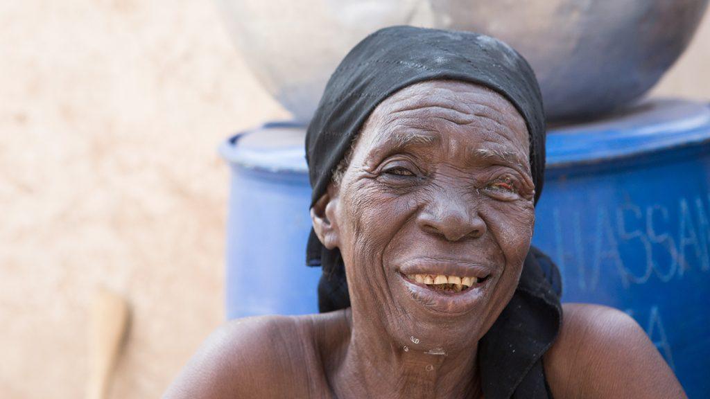 Rahinatu smiles outside her home.