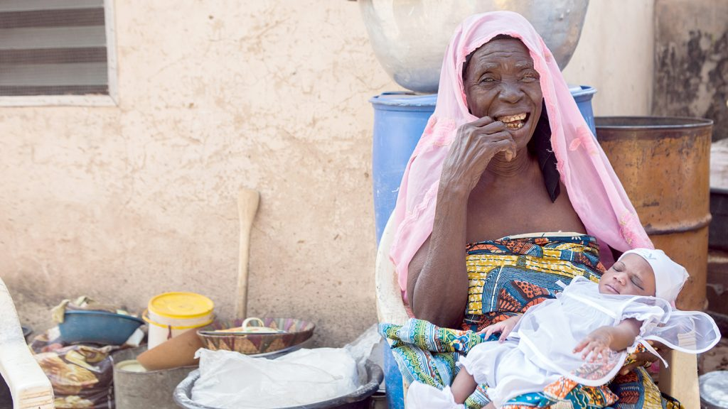 Rahinatu holds her granddaughter and smiles following her trachoma surgery.