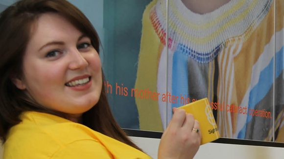 Charlotte from our Supporter Care team smiles while wearing a yellow Sightsavers T-shirt.