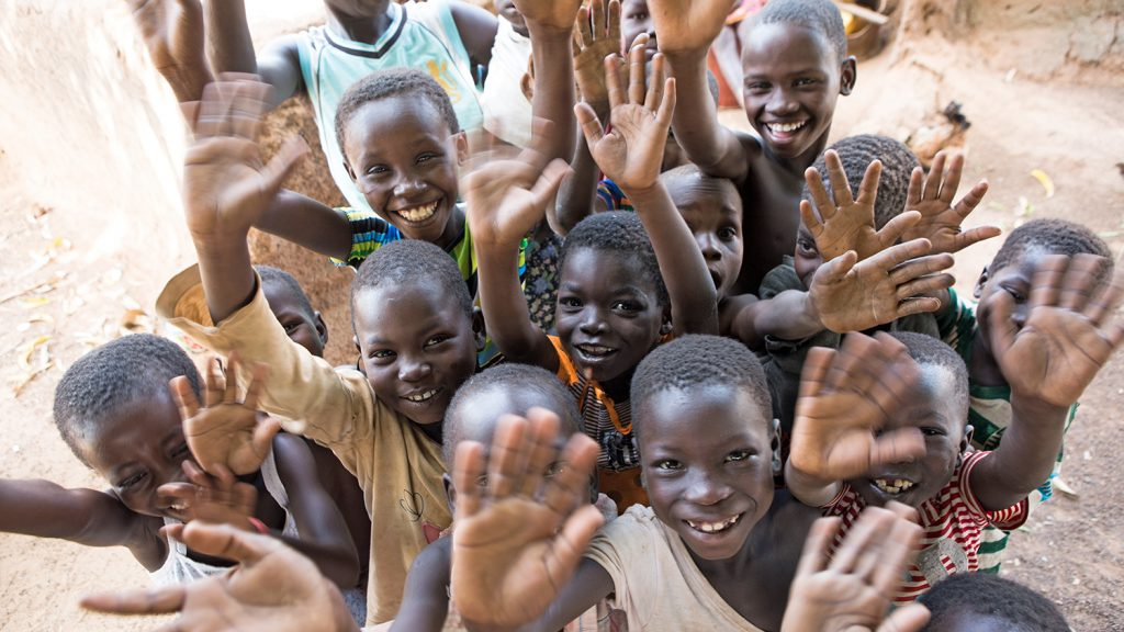 A group of children in Ghana smile and wave at the camera.