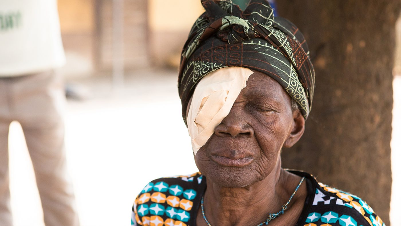 Ayishetu from Ghana sits beside a tree with a patch on her right eye following her trachoma surgery.