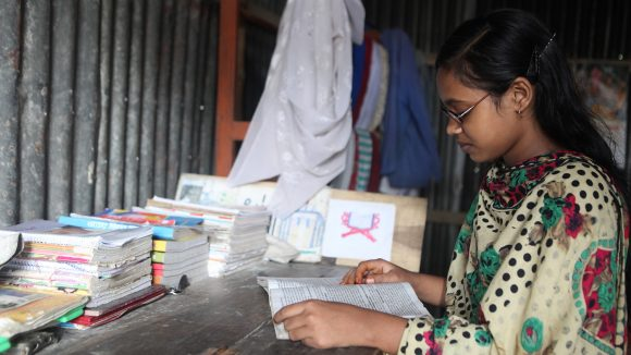 A girl is reading a book at home while wearing glasses.