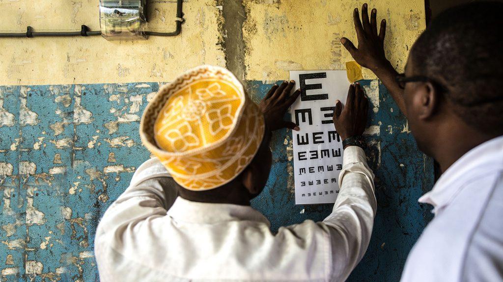 Two teachers prepare a tumbling e-chart for the school children's eye exam.