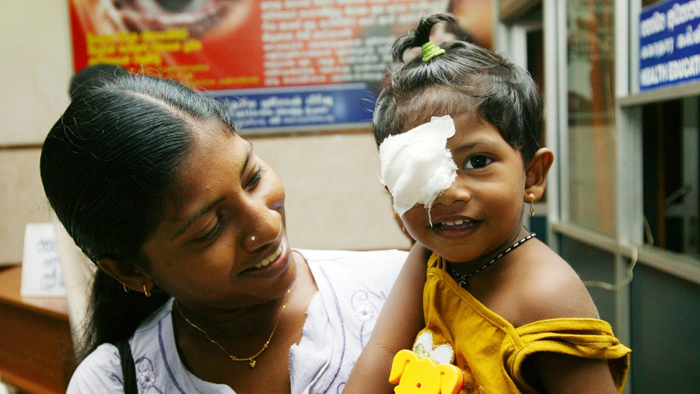 A young toddler smiles with a patch over one eye.