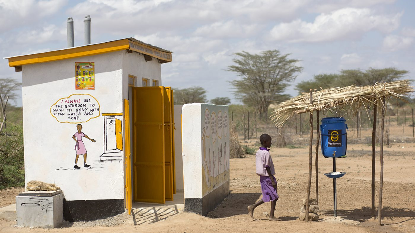 A boy washes his hands after going to the toilet.