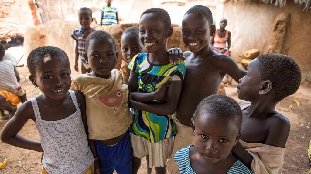 Six children in Ghana stand smiling at the camera.