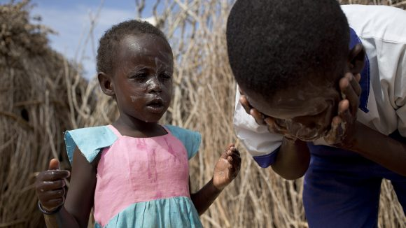 A boy and girl wash their faces outside.