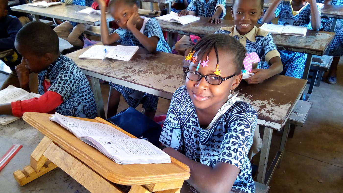 Student Ariane smiles at her desk while wearing her new glasses.