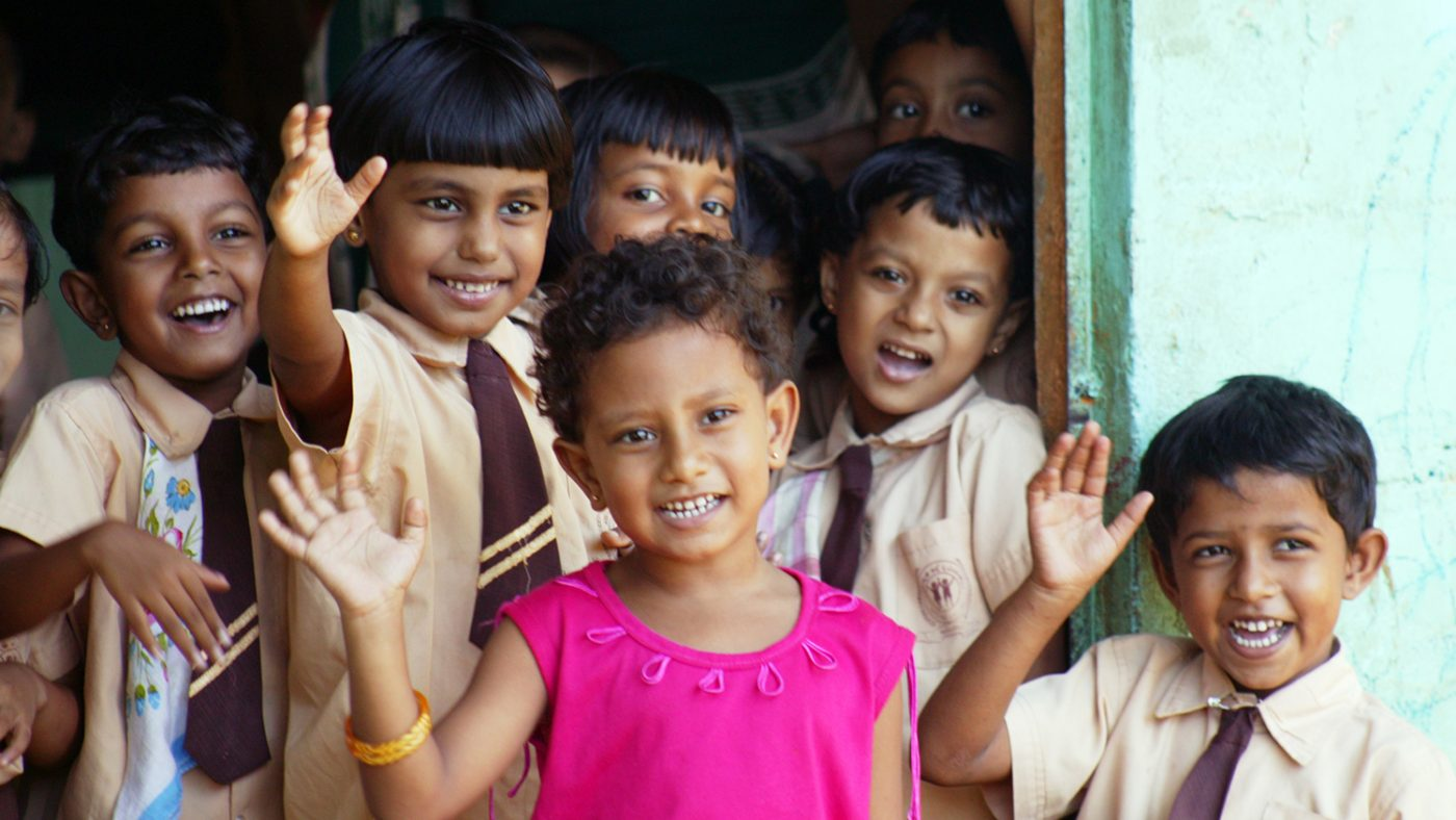 Children laugh and wave outside a classroom.