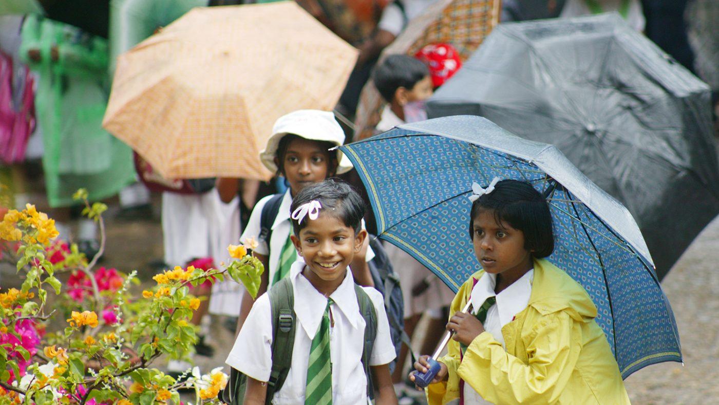 Children in Sri Lanka stand outside in the rain with umbrellas.