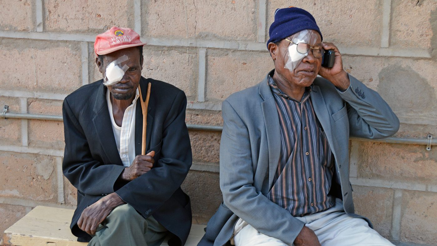 David and a fellow patient sit with bandages on their eyes.