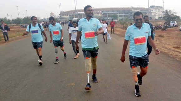 Anwar, who has a prosthetic leg, running alongside other people with disabilities.