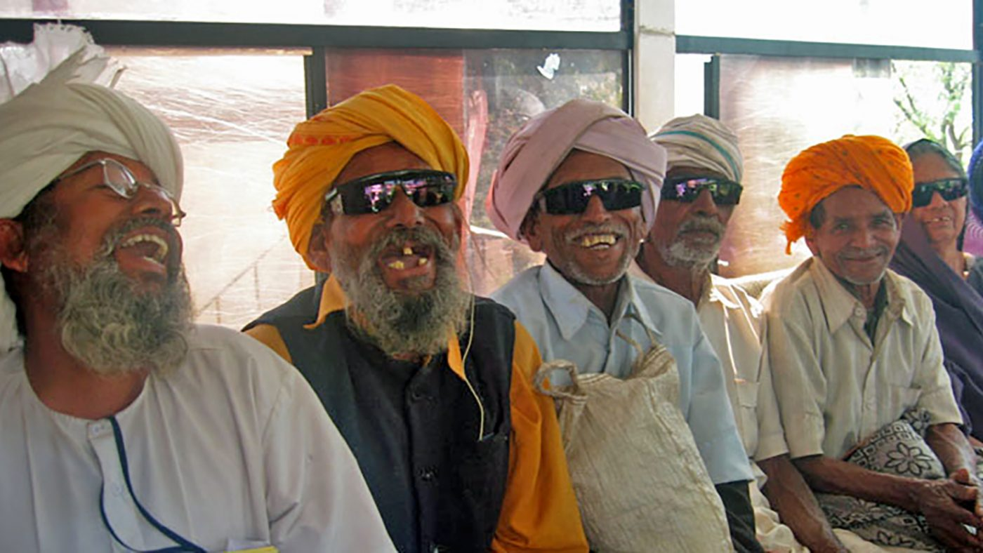 A group of cataract patients smile broadly after surgery.