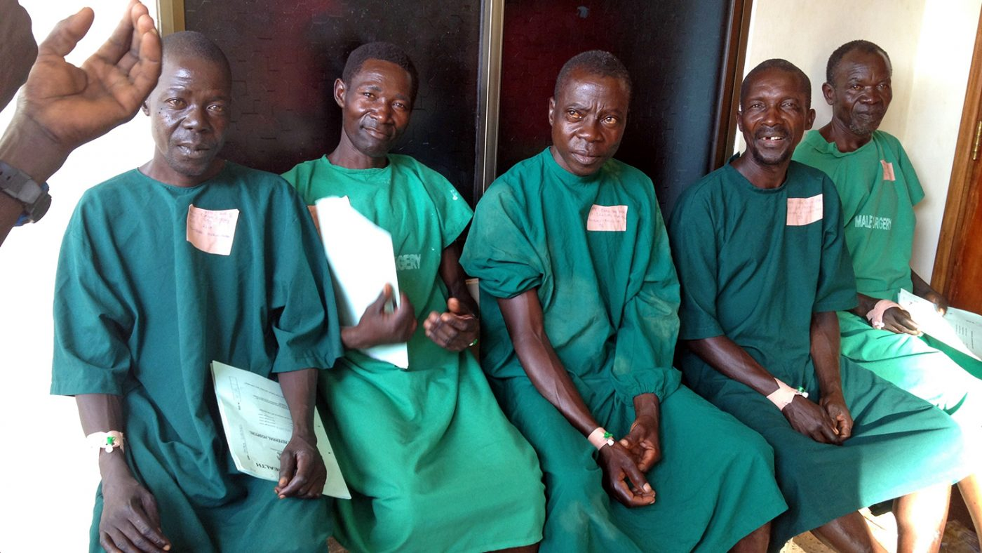 A group of patients in green scrubs wait for surgery.