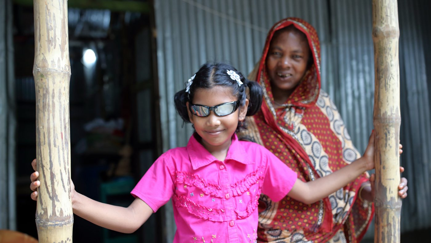 Sumaiya smiles while wearing her new glasses following her cataract operation. Her grandmother looks on from the background.