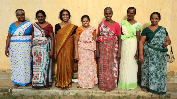 Seven women in a line are smiling.