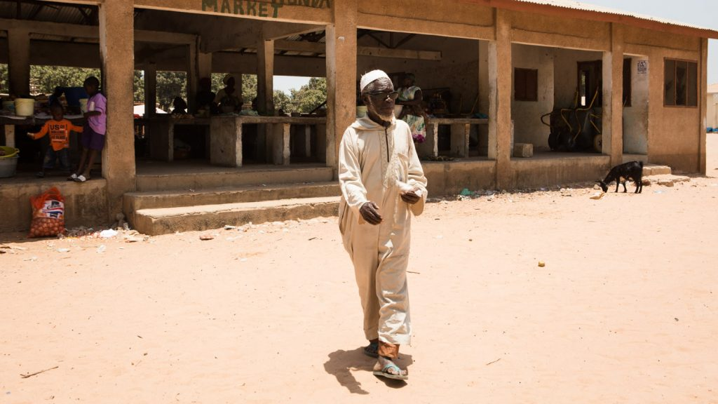 Yaya Manneh walking through his village.
