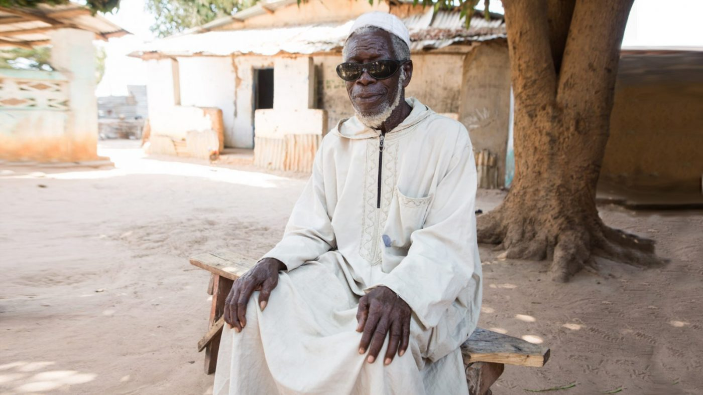 A male trachoma patient sitting outside, smiling.