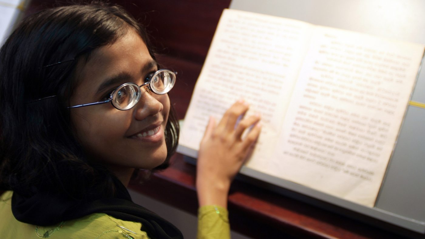 A girl is reading a book, wearing glasses.