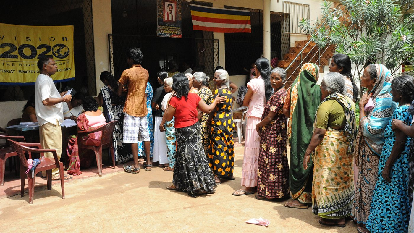 People queue outside a building for eye tests in Colombo.