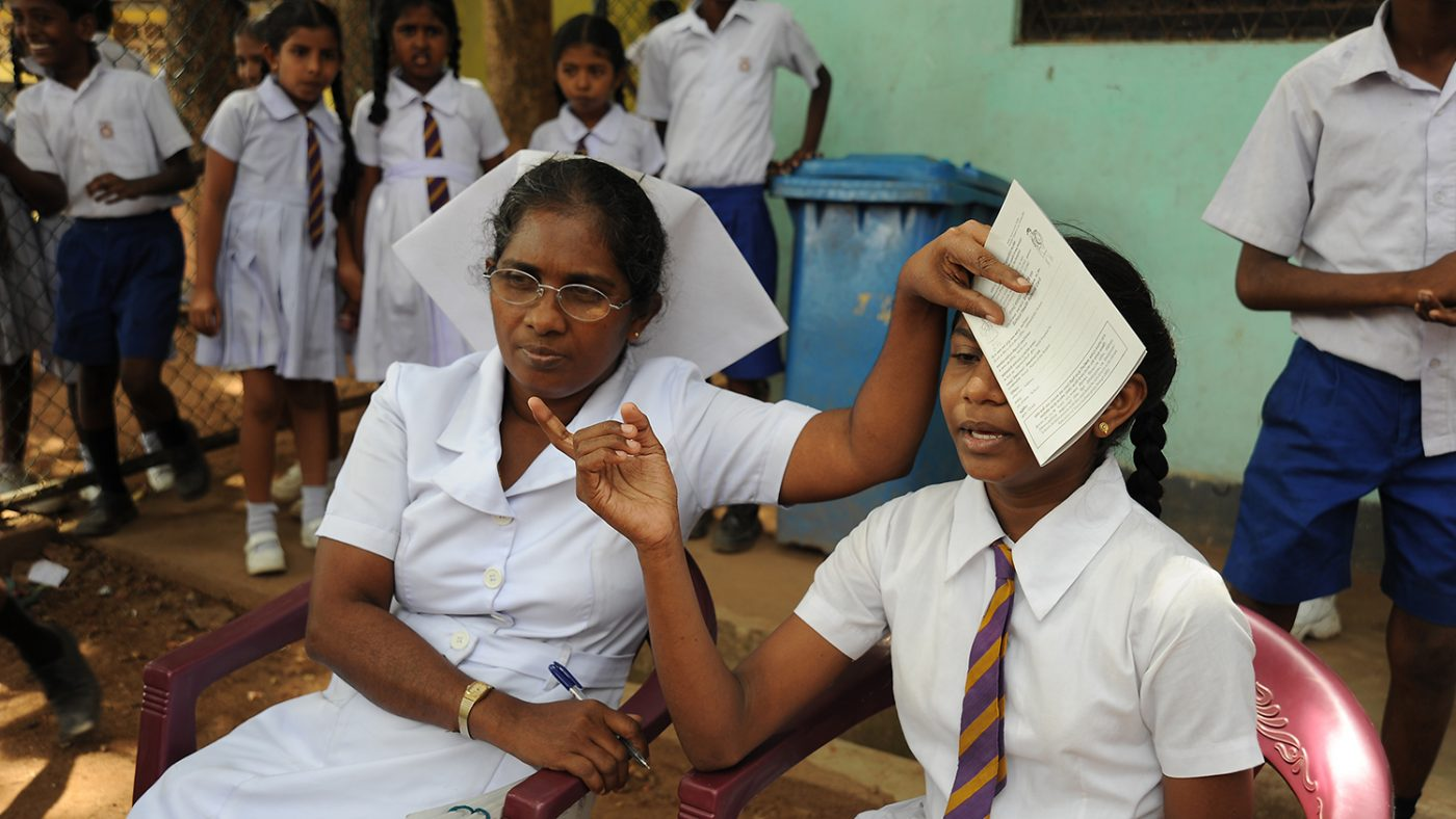 A child is having an eye test, a nurse covers one of the girls eyes.