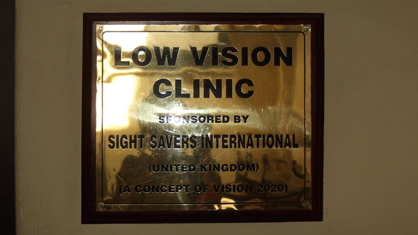 A sign saying 'Low vision clinic, sponsored by Sightsavers international.