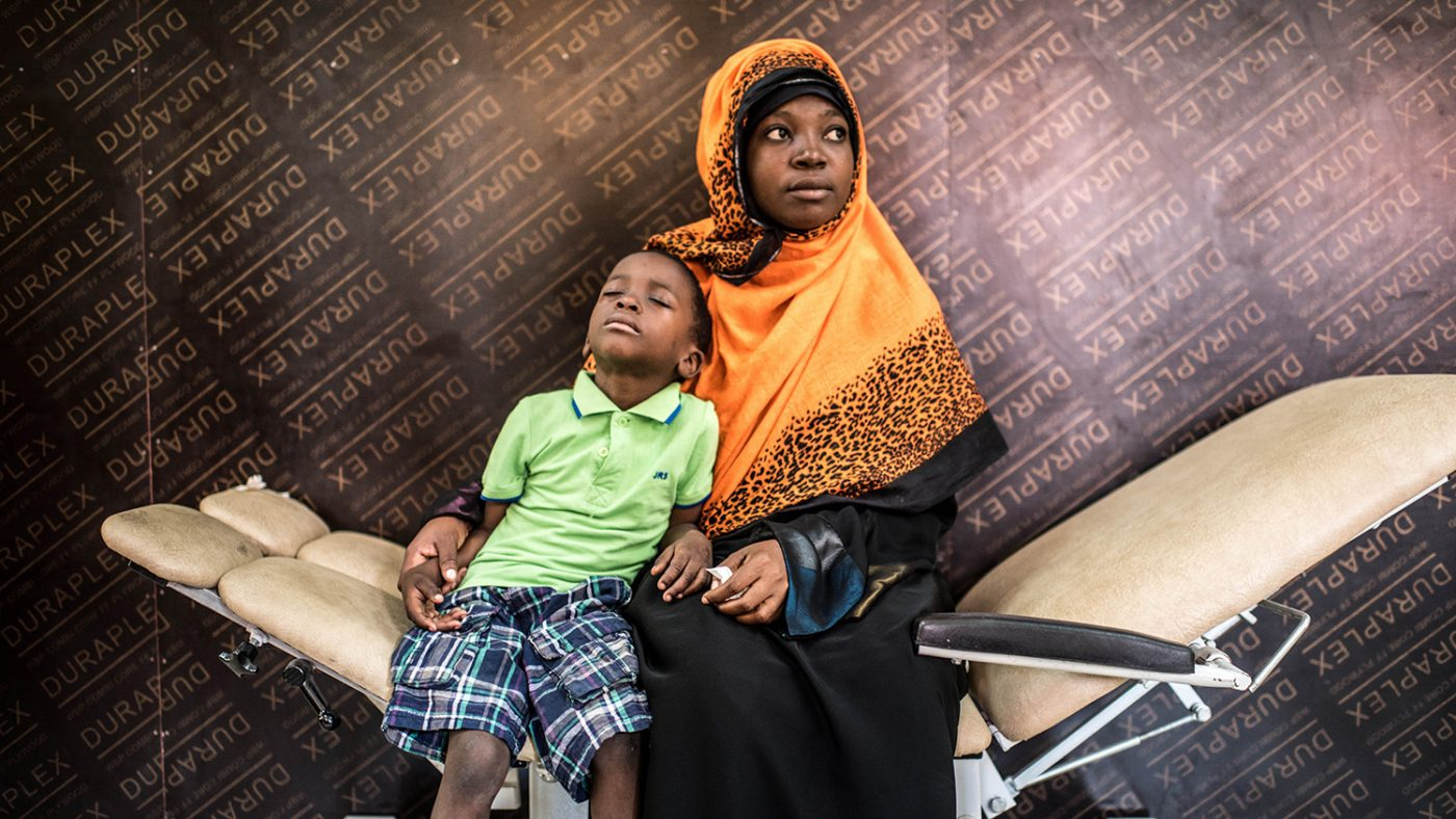 Fahad sits with his mother in a hospital waiting room.