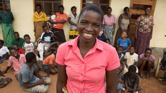 A lady smiling outside a centre in Malawi which provides physiotherapy.