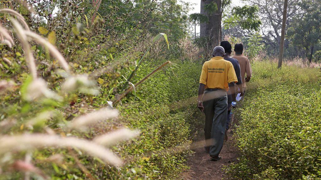 The eye care team walk across a grassy field.