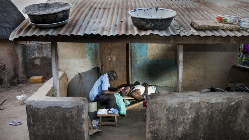A trichiasis patient lies on a table outside his home, while a surgeon operates on his eyes.