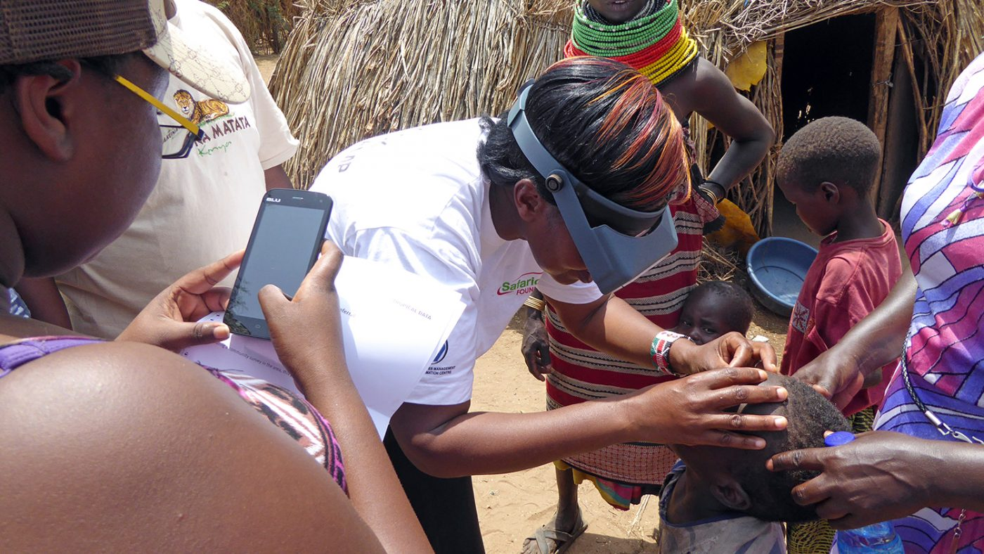 Eye health staff examine a child's eyes and record the results on a mobile phone.