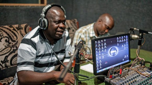 William Mugayo speaks into the microphone during a radio broadcast.