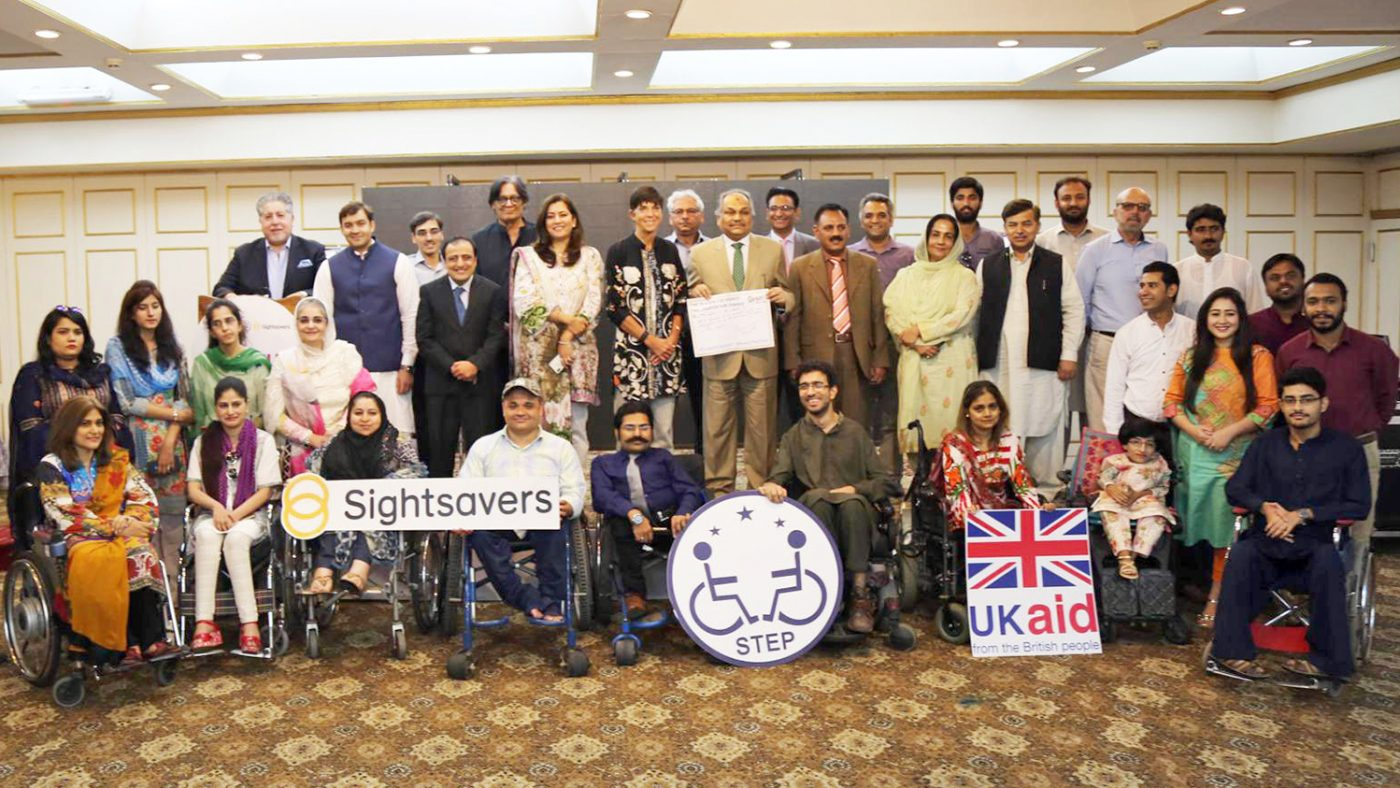 The attendees of the summit pose for a group photo, holding boards featuring the logos of Sightsavers, UK Aid and STEP.