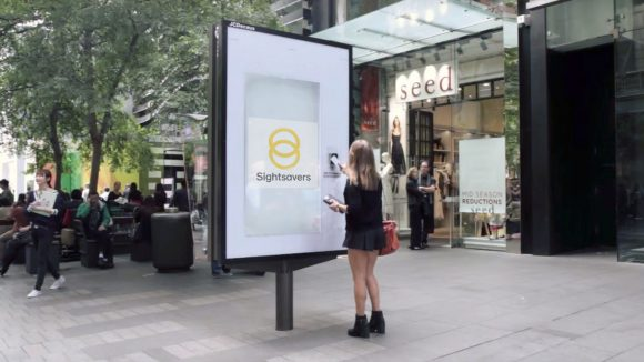 A donation pod in a city centre, with a woman tapping her bank card to make a donation.