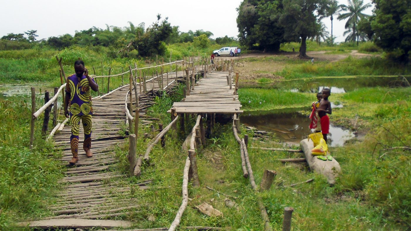 A remote area in Benin featuring a long wooden bridge.